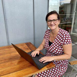Buchhalterin Anke sitzt vor ihrem PC und freut sich über die Spendeneingänge